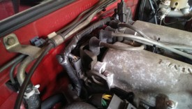 The coil pack is at the back of the engine, the spark plug wires connect to it