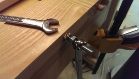 Use two wrenches to break the second nut loose