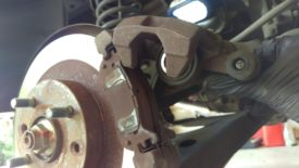 Lift the caliper up, it will pivot on the upper slider pin