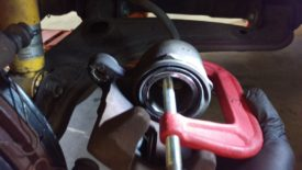 Use a clamp to compress the piston